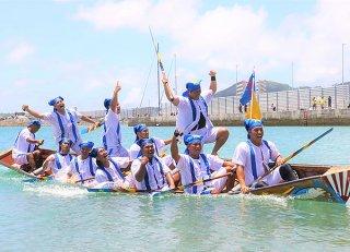 「上がり」を制し、舟上から喜びを表現する中・西合同の西組=6日午後、石垣漁港