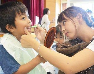 ブラッシング体験を行う親子。正しい歯磨きの方法を学んだ=8日午後、石垣市健康福祉センター