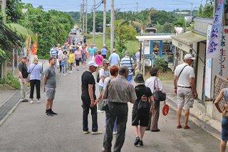 徒歩で移動する大勢の観光客。その間を縫うようにレンタカー(奥)が通行する=5月15日午後、米原のヤエヤマヤシ群落