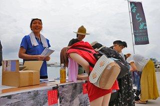 「(仮称)コンドイビーチホテル」の建設中止を求め署名する来島者ら=23日午前、竹富東港