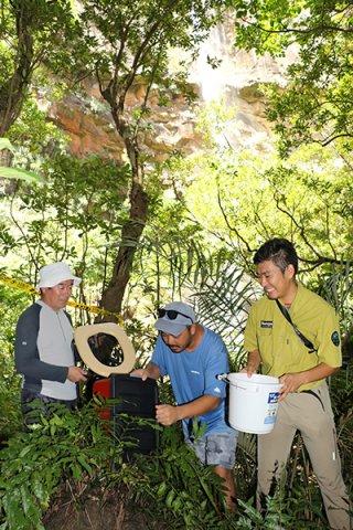 携帯トイレを設置する環境省西表自然保護官事務所職員と西表島カヌー組合の組合員=29日午前、ピナイサーラの滝下
