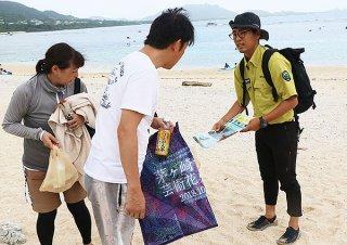 海岸利用者に熱帯魚の捕獲やサンゴの踏み荒らしに注意を呼びかける=6日午後、米原海岸