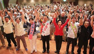 手を取り合って「頑張ろう」を三唱する支持者ら=10日夜、市民会館中ホール
