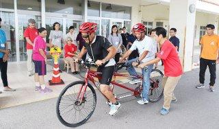 石垣市初の視覚障害者サポーター養成講座でタンデム自転車を体験する受講者=15日午後、石垣市健康福祉センター入口前