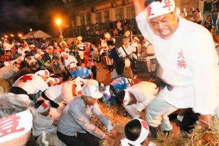 上村と下村に分かれて長さ130メートルの大綱を引き合う住民ら。上村が下村の3連覇を阻んだ=23日夜、崎原道路