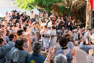 雄雌の綱に棒を差し込んだ後、棒貫人(ブルピトゥ)の東嵩西のり子さんをガーリーで祝福する女性たち=26日夕、真乙姥嶽前