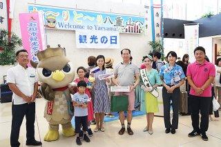 2019番目に到着した土井拓人さん家族ら。記念品を受けた=1日午後、南ぬ島石垣空港