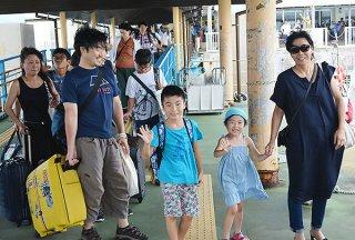 船の便が再開し、笑顔で船に乗り込む観光客ら=10日午後、ユーグレナ石垣港離島ターミナル