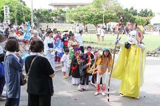 弥勒を先頭に豊漁豊作を祈願しながら歩く前組の行列「ミチサネ」=14日午前、波照間公民館前