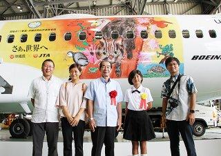 飛行機にラッピングされた池村愛音さん(右から2人目)の作品=8月31日午前、那覇空港内JTAメンテナンスセンター