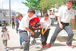 市民防災訓練で避難してきた親子を手助けする生徒ら=1日午前、大浜中学校