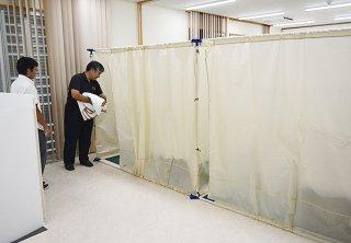 避難者のプライバシーに配慮して間仕切りを設置し、毛布を配布する職員=5日午後、結い心センター