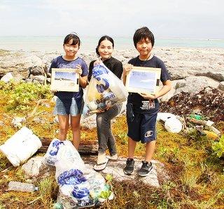 真栄里海岸で8月の1カ月間、調査を兼ね海岸清掃を行った一般社団法人ビーチクリーンロボットプロジェクト海岸工学会会員のはやのん氏(中央)ら=6日午後、同海岸