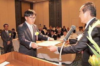 米盛博明支部長(右)から永年会員表彰を受ける会員=12日夜、アートホテル石垣島