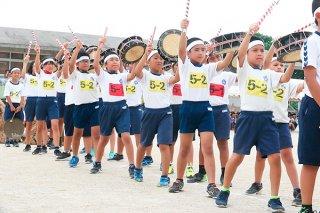 石小ふるさと祭りで力強い太鼓を披露する5年生ら=15日午後、同校運動場