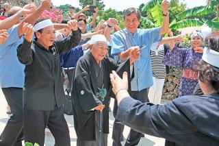 ガーリーで謝花喜一郎副知事を迎え、喜びを表す竹富島の人たちと赤山喜介さん=15日午後、赤山さん宅の庭