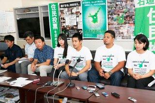 提訴後に会見する原告と代理人。金城龍太郎代表(中央)は「どうしても実現したい」と語る=19日午後、県庁記者クラブ
