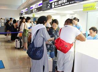 チェックインカウンターで搭乗や空席待ちの手続きをする利用者ら=21日午後、南ぬ島石垣空港