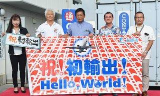 石垣-台湾間の出荷スタートを、「祝初輸出」の幕を掲げて喜ぶ関係者たち=2日午前、石垣空港貨物代理店