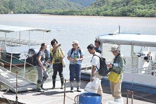 環境省職員から浦内川について説明を受けるウルリーカ・オーバリ氏(左)とウェンディー・アン・ストラーム氏(左から3人目)=11日午後、浦内川