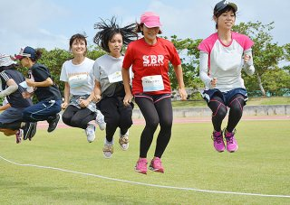 大縄跳びで軽快なジャンプを見せる参加者たち=14日午前、石垣市中央運動公園陸上競技場