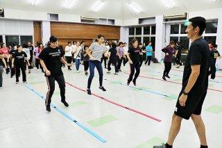 津田幸保さん(手前右)の指導の下、リズムジャンプを体験する参加者ら=21日夜、大川公民館