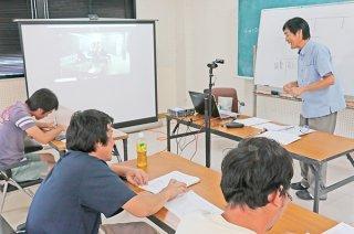 ICTを活用してビデオ通話による農業簿記講習会が開かれた。左奥のスクリーンは波照間島の会場=24日午後、西表離島振興総合センター