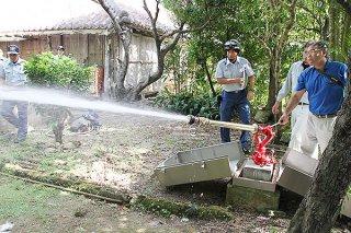 旧宮良殿内の敷地内で放水銃の機能を点検する石垣市消防本部と市文化財課の職員ら=13日午後、同所