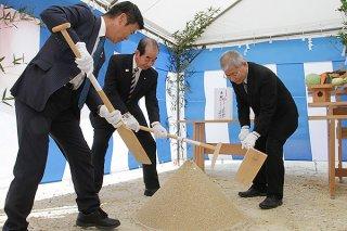 仮庁舎起工式でくわ入れを行う西大舛髙旬町長(中)ら=13日午後、美崎町