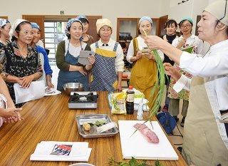 講師の嵩西氏(右)から命草を使った郷土料理を学ぶ受講生ら=21日午後、伊原間公民館