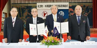 友好交流協定を締結式した外間町長(右から2人目)と小野町長(同3人目)=11月30日午後、久部良多目的施設