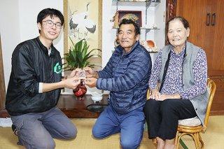 玉木陸斗さん(左)からもちきびの種を受け取る大浜永太郎さん、石垣リツさん=5日午後、川平の大浜さん宅