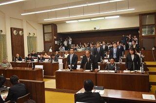石垣市自治基本条例の廃止案に起立して賛成する与党(右側)の10人。賛成少数で否決された=16日午後、本会議場