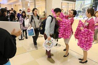 初便で到着した客をピンクの花をかたどったレイで歓迎するピーチ・アビエーションの客室乗務員ら=26日夜、南ぬ島石垣空港