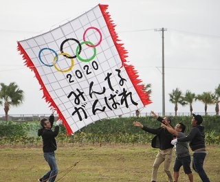 五輪の成功を願い、すべての人にエールを書き込んだ自由だこ。強風の中、高く揚がった=12日午前、南ぬ浜町