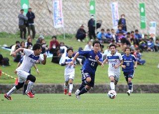 海邦銀行SC(白)と練習試合を行う横浜F・マリノス(青)。2試合目出場のMF仙頭啓矢がドリブルで突破する=19日午後、サッカーパークあかんま