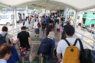 西表島を訪れる観光客。世界遺産登録後に予想される入域増に対し、県が観光管理計画を進めている=2019年5月20日、上原港
