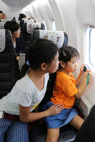 西表島上空の遊覧飛行に参加した児童ら=26日午後