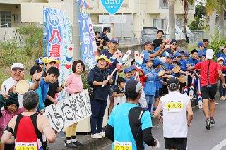 横断幕を広げハーリーの櫂(かい)を振り声援を送る八島小学校の児童や保護者ら=26日午前、国道390号バイパス