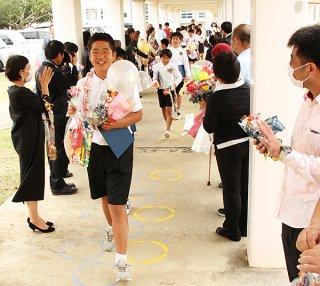 宮良小学校で卒業式を終え保護者らの祝福を受けながら退場する卒業生ら=20日午前、同校