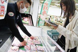 200㌘900円と割り引き対象になっている石垣牛を確認する女性客=11日午後、JAファーマーズマーケットやえやまゆらてぃく市場
