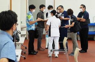 新型コロナウイルス感染症相談外来の開設を準備する医療関係者ら=17日午前、石垣市中央運動公園野球場