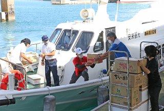 生活必需品を船に積み込む事業者ら=3日午後、石垣港離島ターミナル