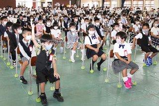 入学式で名前を呼ばれ元気よく返事する新1年生=12日午前、登野城小学校体育館