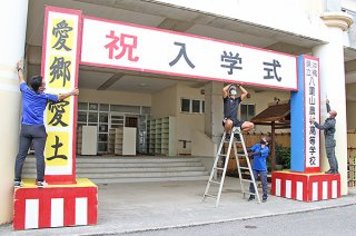 学校再開に向けて入学式の準備を行う八重山農林高校の教職員ら=20日午後、同校