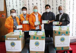 マスクを寄贈した八重山ライオンズクラブ東郷会長(中央)ら=25日午後、石垣市役所