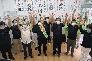 万歳をして2期目当選を喜ぶ次呂久成崇氏(中央)と支持者ら=29日午後5時すぎ、新川の選対本部事務所