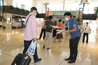 到着した来島客らに感染予防対策のチラシを配布する市職員ら=1日午後、南ぬ島石垣空港