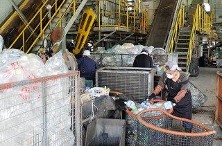 ふたを外したペットボトルを移動させる作業員=2日午後、石垣市一般廃棄物最終処分場