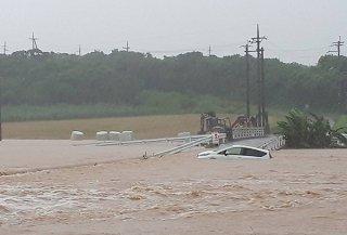 轟川が氾濫し、道路上で水没する車両。濁流が流れる=8日午前10時ごろ、牧那真(まきなま)橋近く(読者提供)